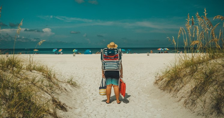 man with beach equipment on his back, walking towards the beach