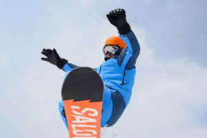 snowboarder flying over top of photographer